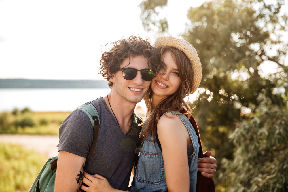 Portrait of smiling young hipster couple standing against trees and sea on the background