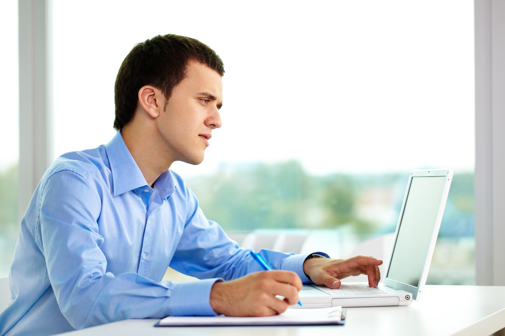 Portrait of successful businessman working on computer in office