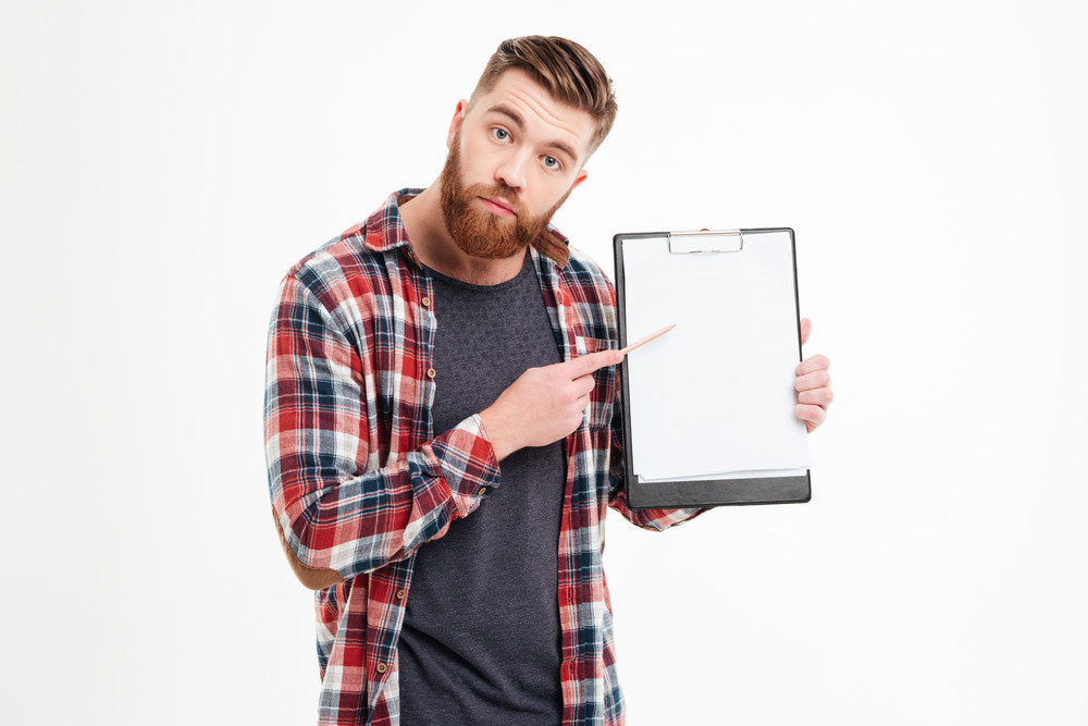 Portrait of upset casual bearded man in plaid shirt pointing pencil at blank clipboard
