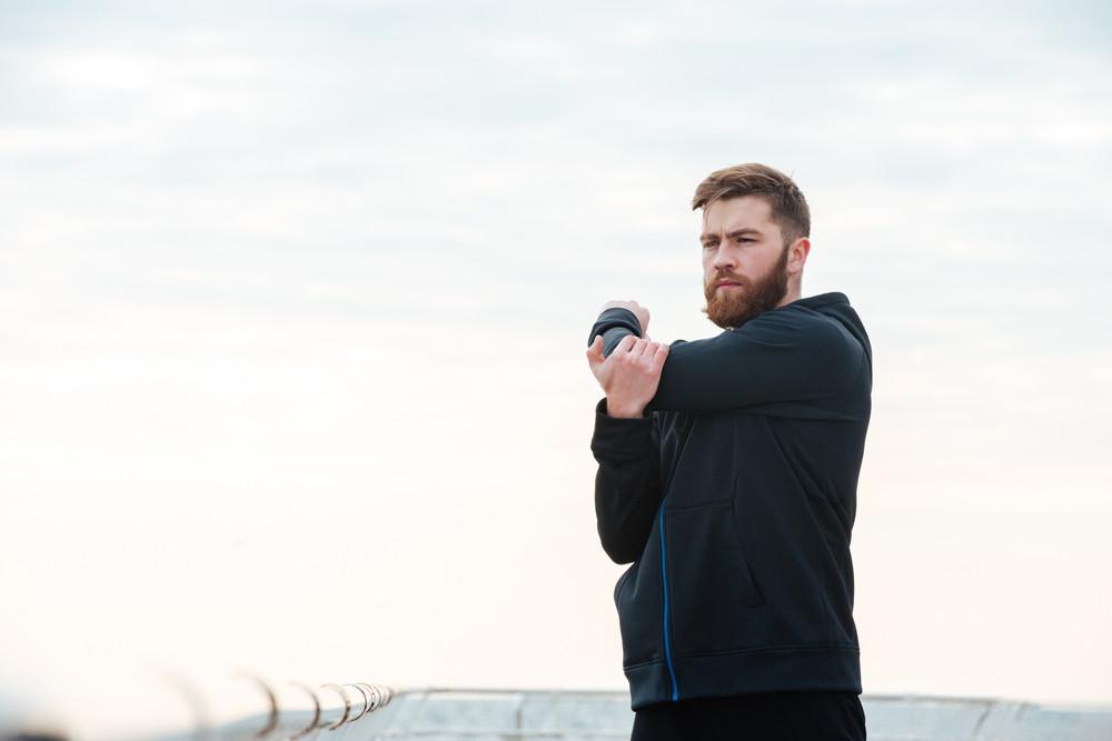 Portrait of warming up runner. looking away.