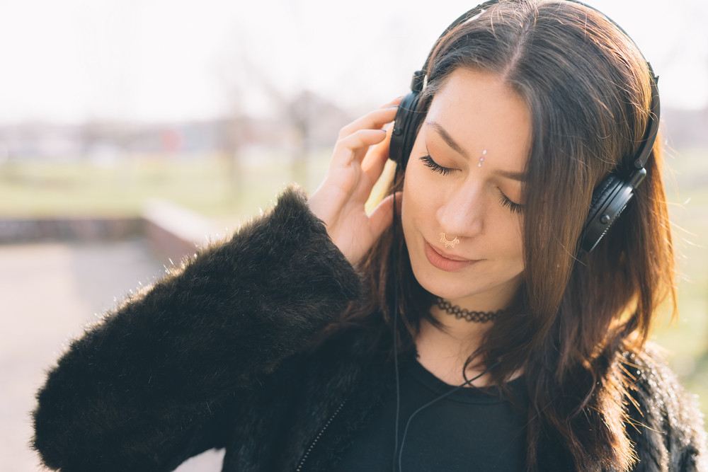 Portrait of young beautiful caucasian long brown hair woman with septum piercing outdoor listening music, eyes closed - music, relaxing, carefree concept