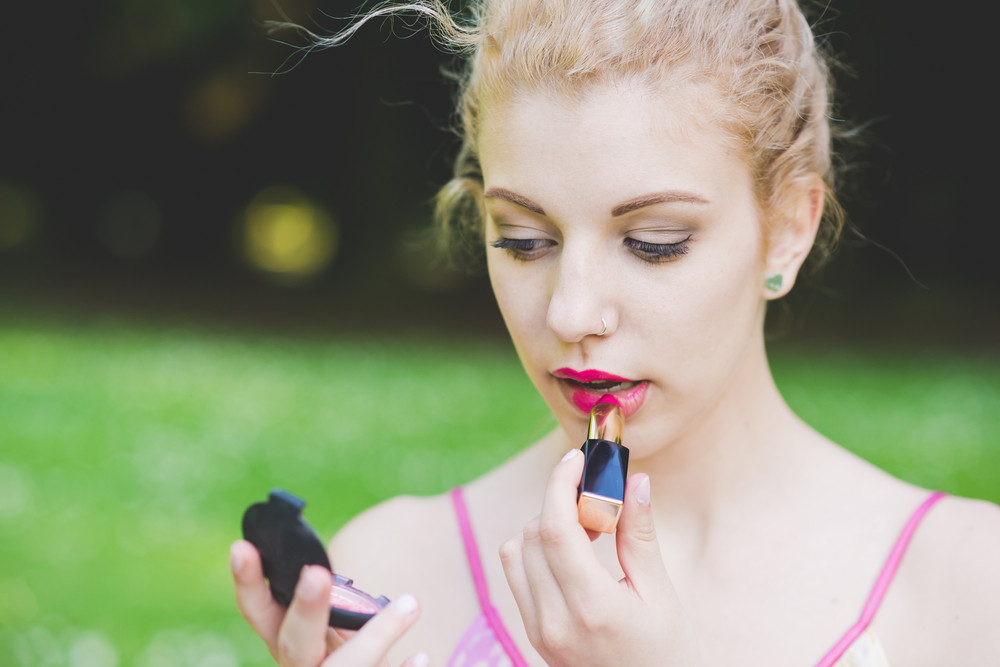 Portrait of young beautiful caucasian pale blonde hair woman outdoor putting make up on - vanity, beauty, skin care concept
