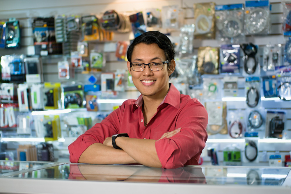 Portrait of young chinese man working as clerk in computer and technology store, smiling at camera and leaning on desk in shop