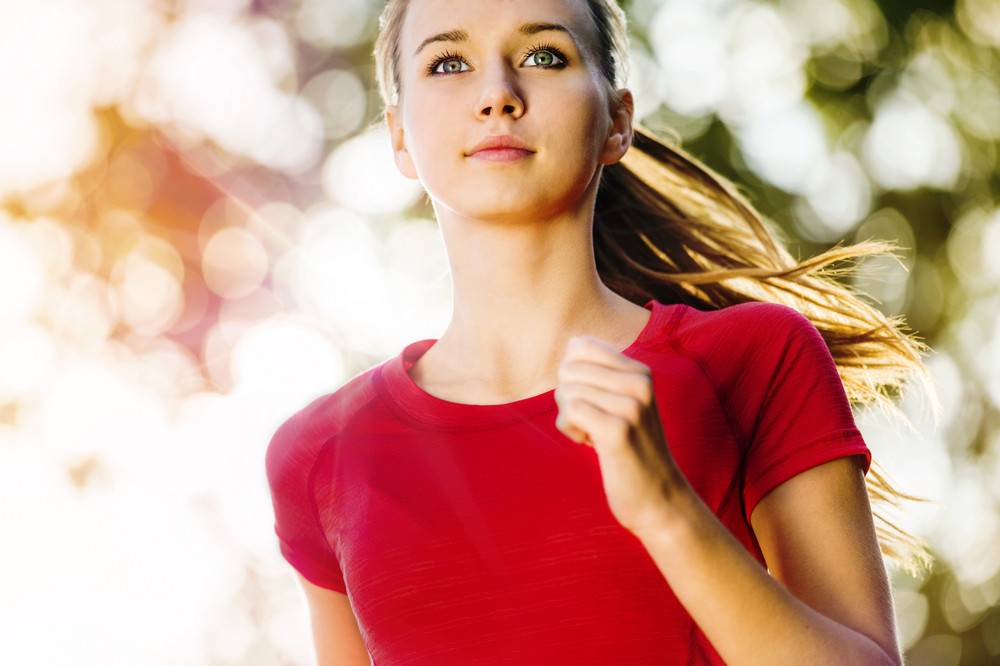 Portrait of young female runner jogging in the city.