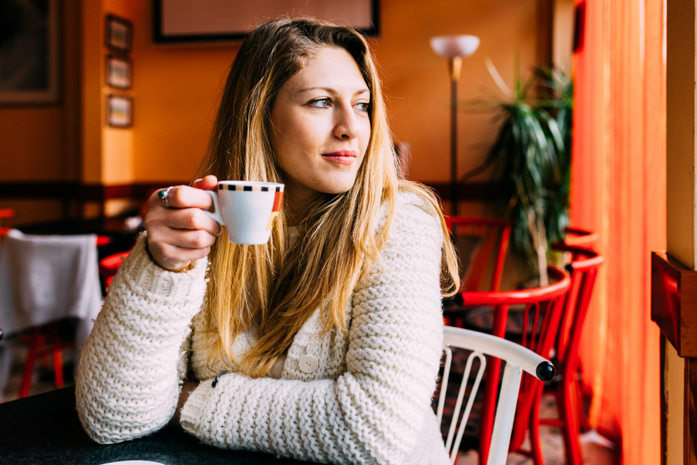 Portrait of young gorgeous female drinking coffee and looking with smile out of the coffee shop window while enjoying her leisure time - break, happiness, serene concept