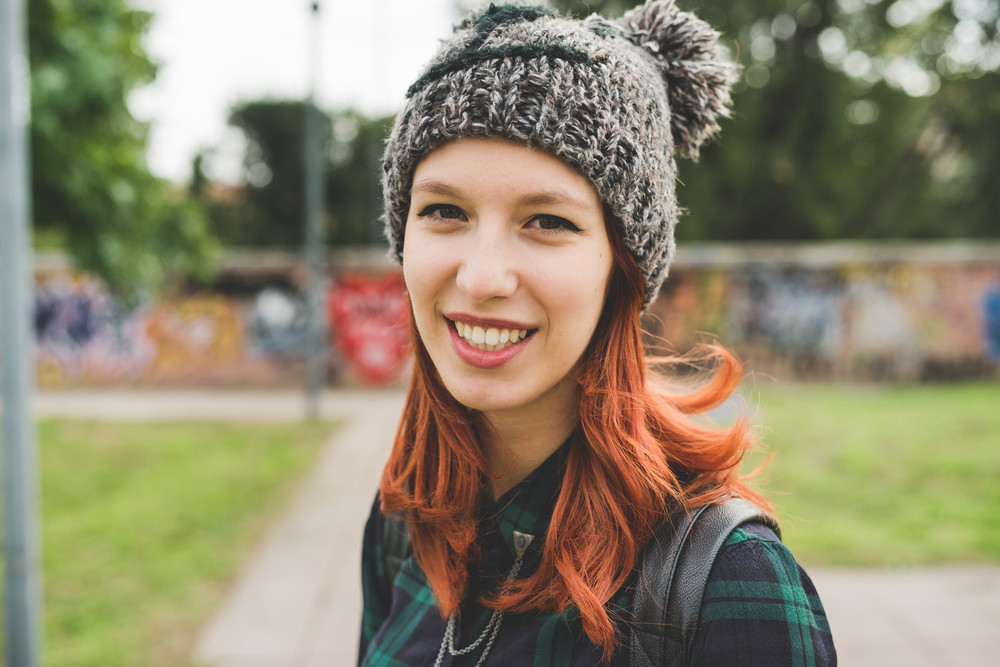 Portrait of young handsome caucasian redhead straight hair woman wearing hat looking in camera smiling - carefree, youth, having fun concept