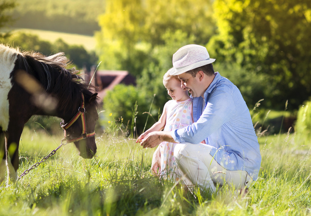 Portrait of young happy father with his dauhter at countryside outdoors, feeding pony