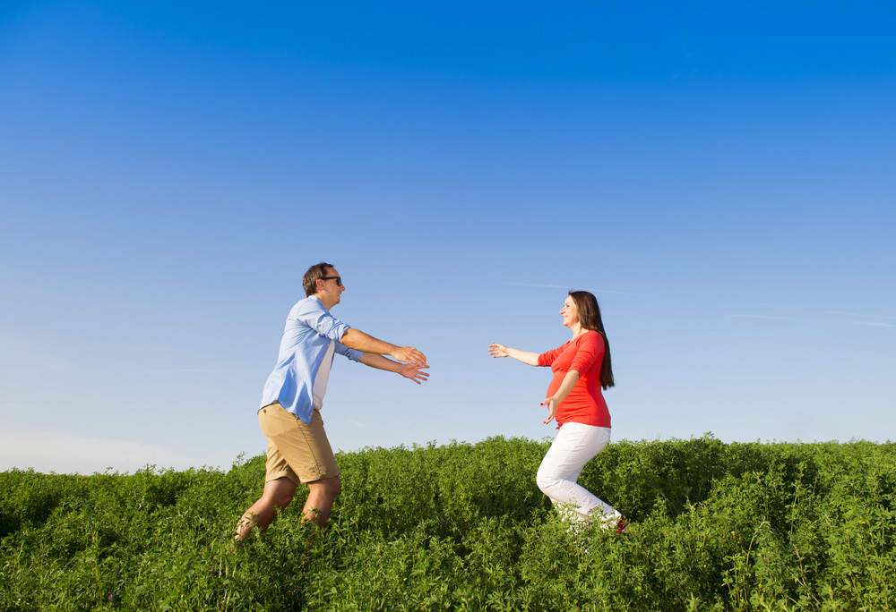 Portrait of young pregnant couple with blue sky