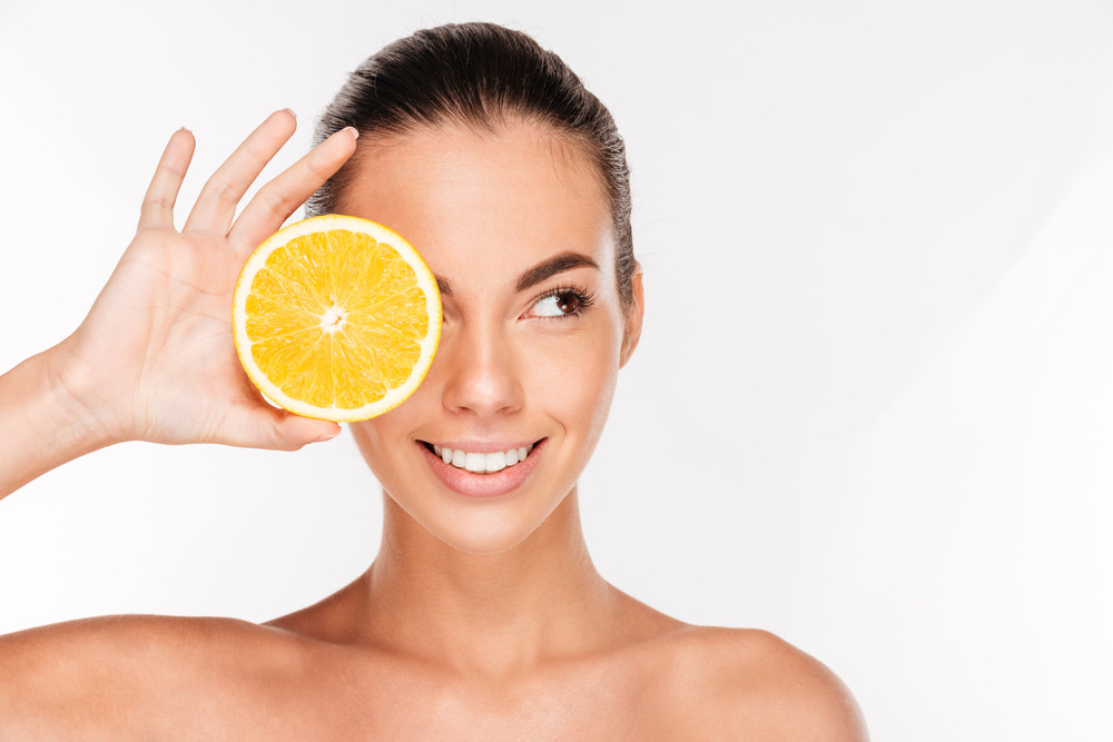 Portrait of young smiling woman cover her eye with orange isolated on a white background