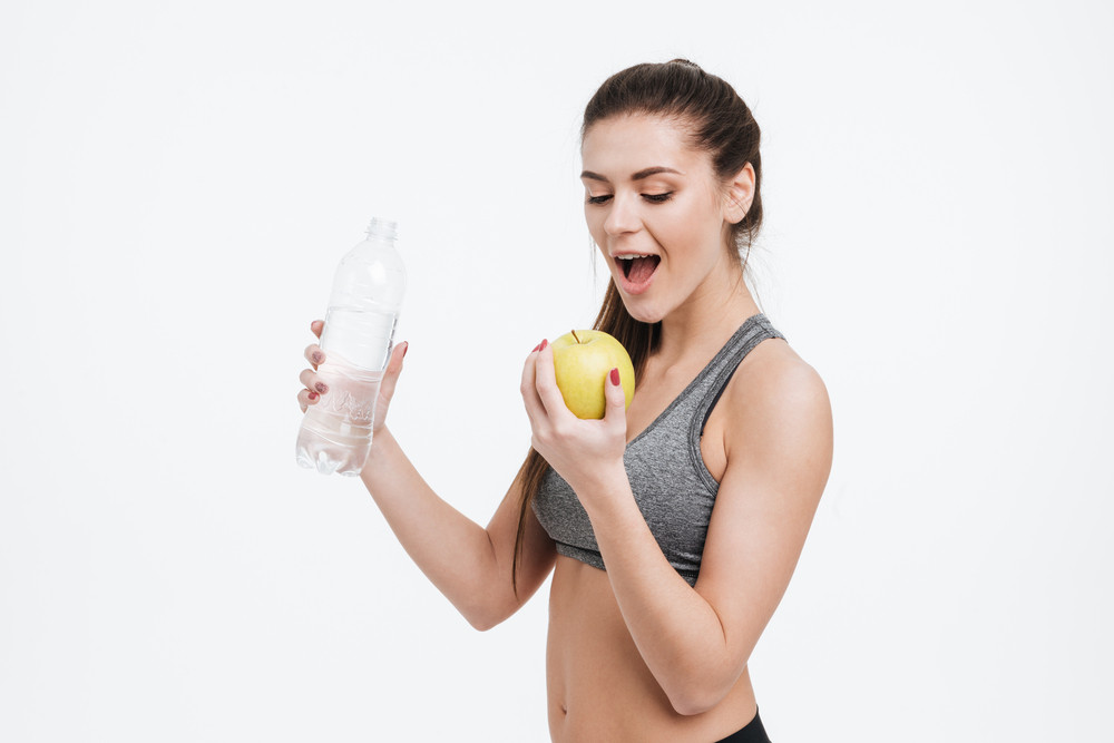 Portrait of young sports woman holding water bottle and biting apple isolated on a white background