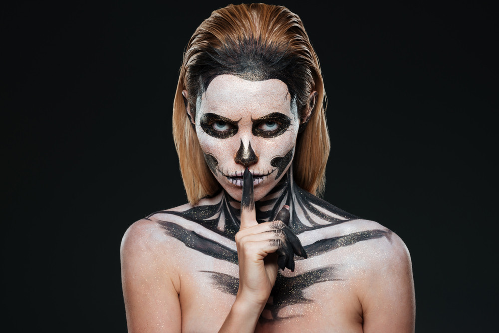 Portrait of young woman with gothic skeleton makeup showing silence gesture over black background