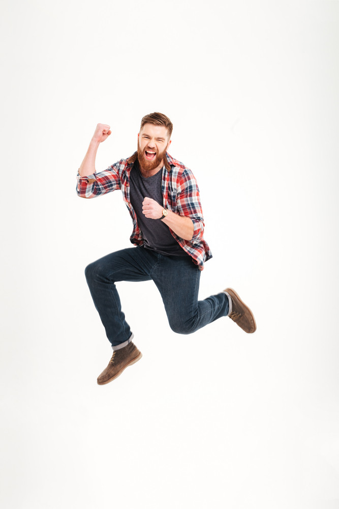 Positive cheerful carefree casual young man in plaid shirt jumping in the air and smiling