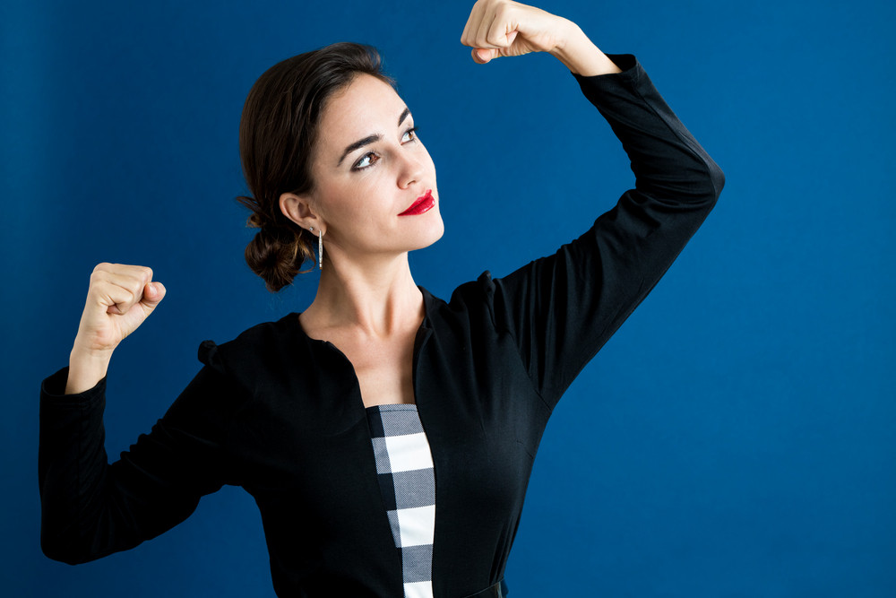 Powerful young woman on a dark blue background