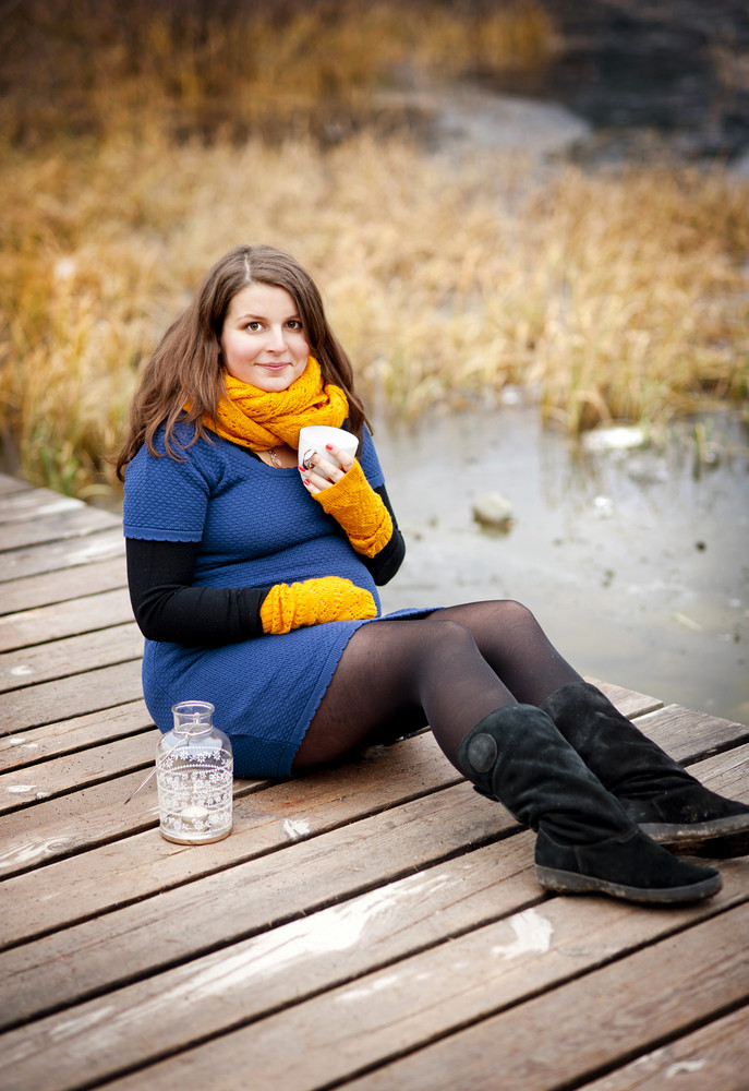 Pregnant woman in autumn clothes sitting on pier and drinking hot drink