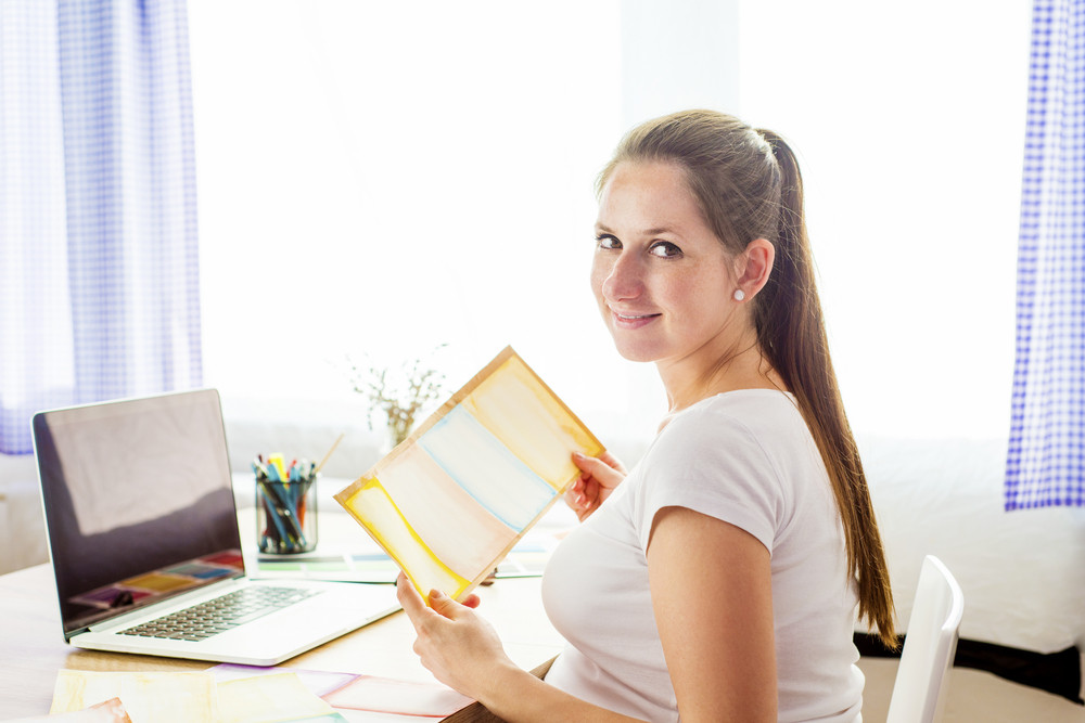 Pregnant woman in home office with laptop