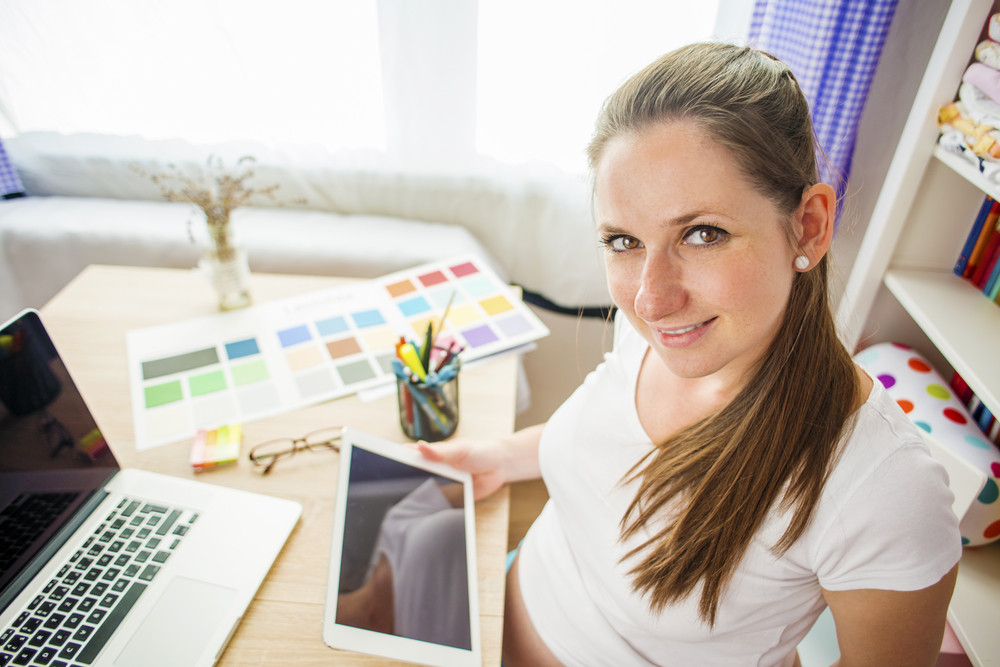 Pregnant woman in home office with tablet