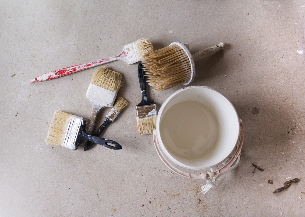 Preparing to paint the wall. Detail of paintbrush and bucket of color on the floor.