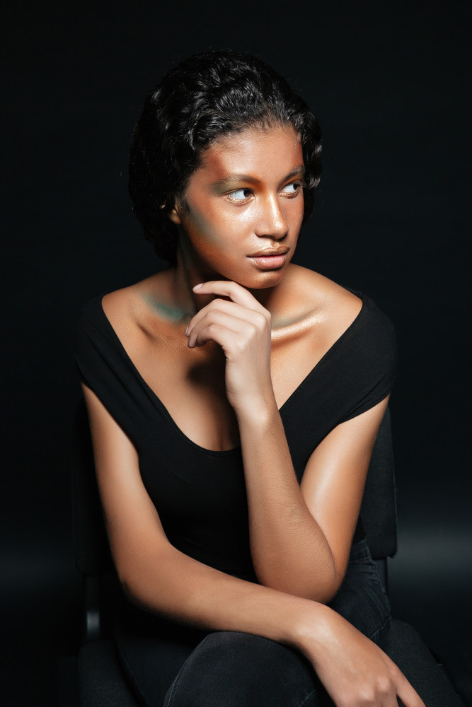 Pretty african american young woman with creative makeup posing on chair over black background