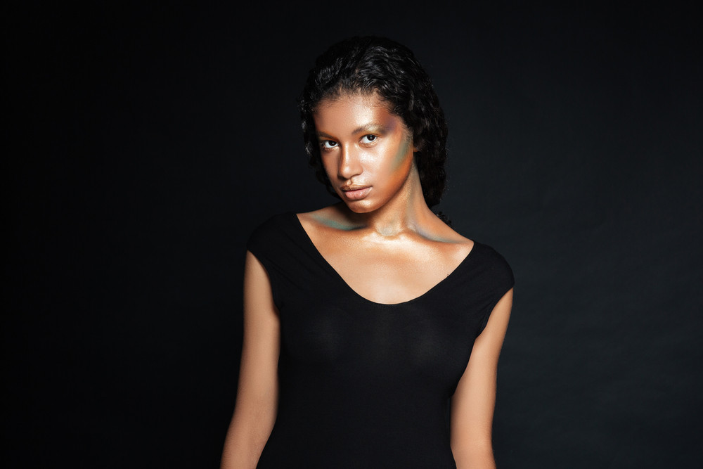 Pretty african american young woman with shining makeup standing over black background