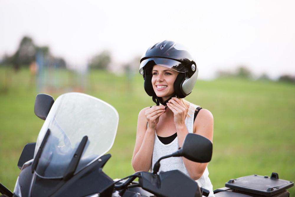 Pretty blond woman enjoying a motorbike ride in countryside, taking off helmet.