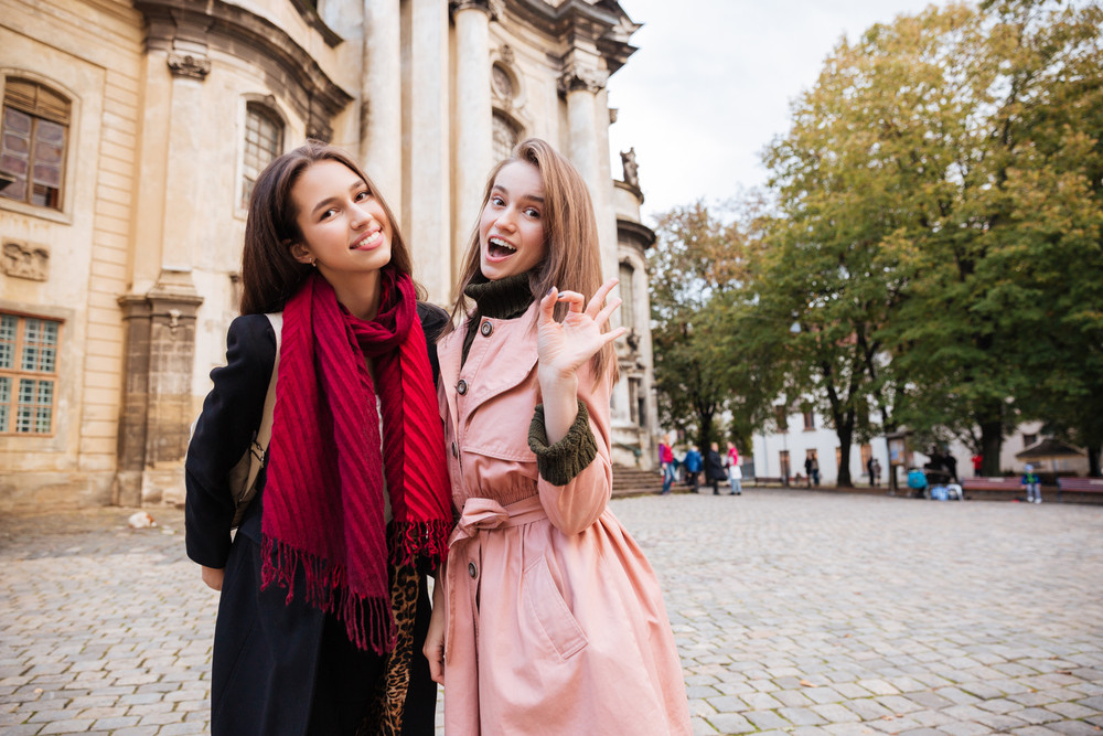 Pretty girls in coats on the street. looking at the camera