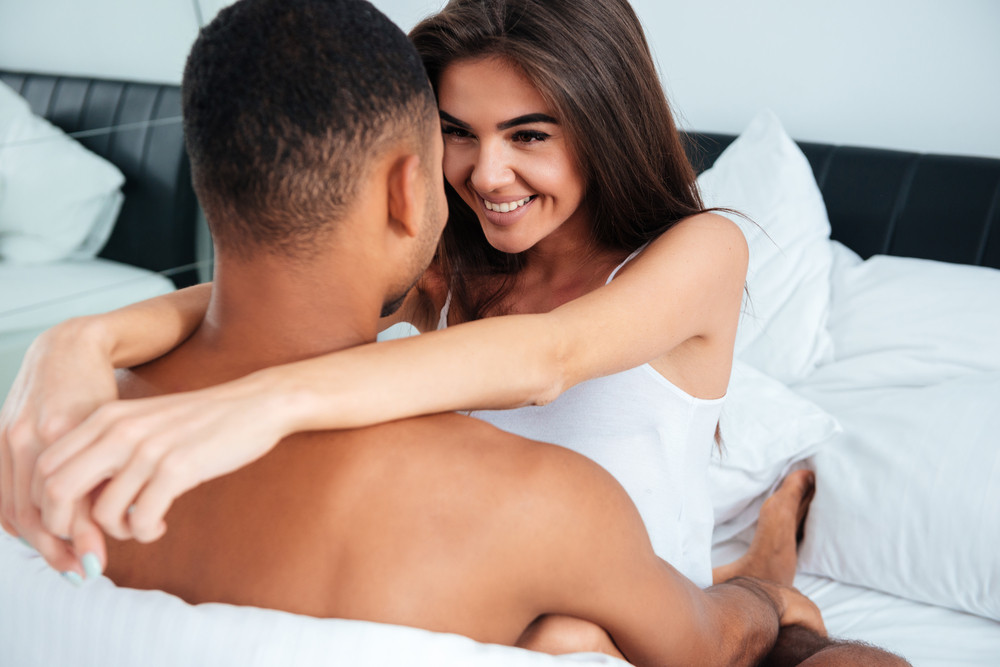 Pretty interracial couple in bed. eyes to eyes. smiling girl. white bedroom