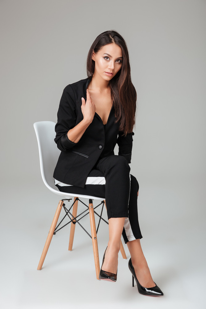 Pretty model on chair looking at camera. fashion. gray background