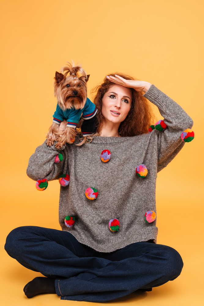 Pretty ouong woman with red hair sitting with her dog and looking far away isolated on orange background