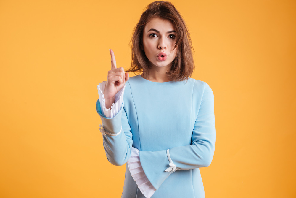 Pretty playful young woman pointing up and having an idea over yellow background