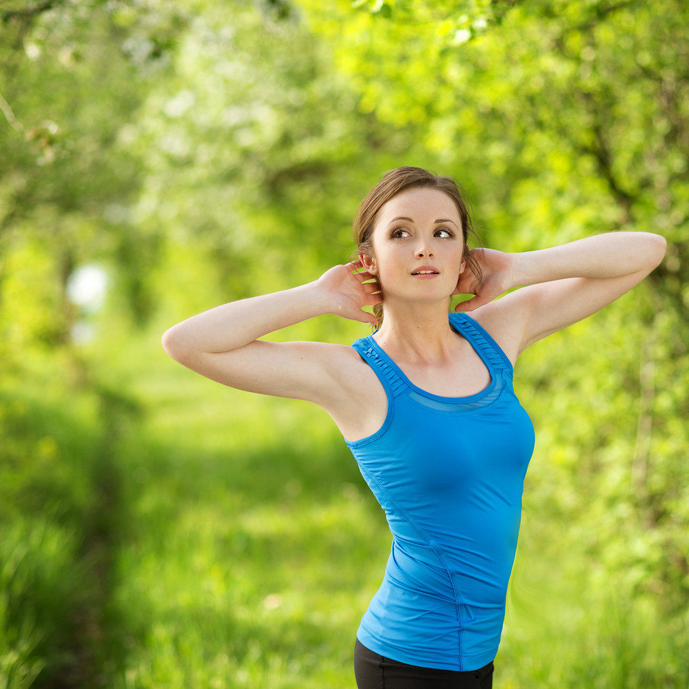 Pretty young athlete is doing exercise in nature