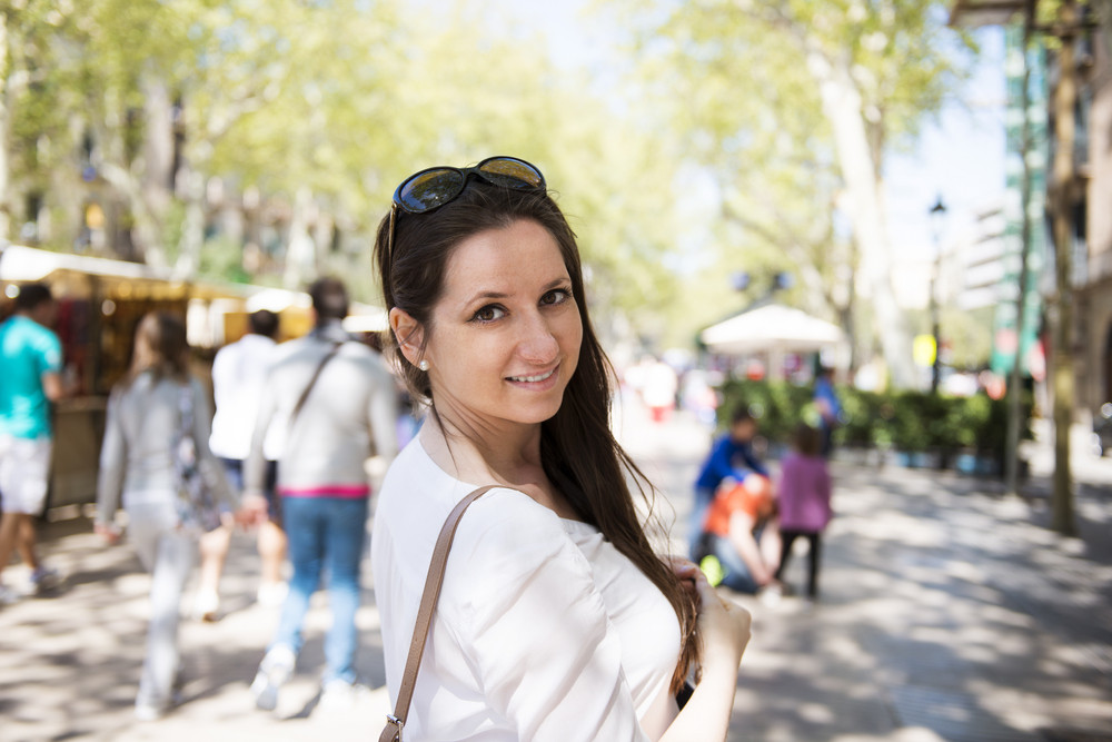 Pretty young female tourist is enjoying vacation in Barcelona city, Spain.