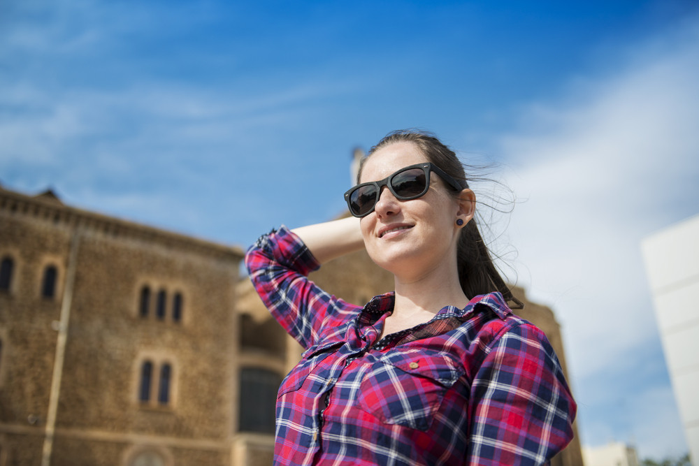 Pretty young female tourist posing in front of the church in Barcelona, Spain.