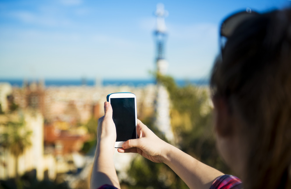 Pretty young female tourist takes picture in Parc Guell in Barcelona, Spain.