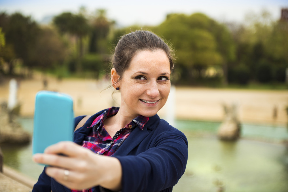 Pretty young female tourist taking selfie in front of the fountain in Barcelona, Spain.