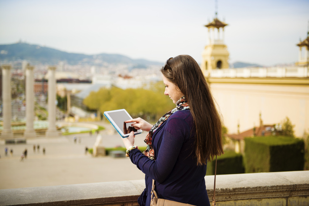 Pretty young female tourist using digital tablet and enjoying the view in Barcelona, Spain.
