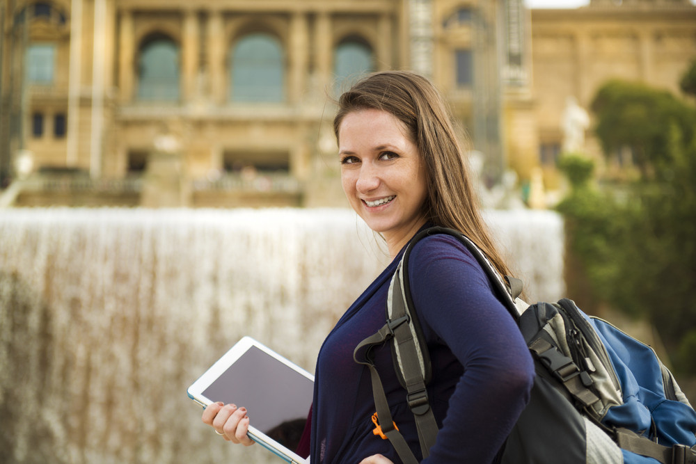 Pretty young female tourist using digital tablet and posing in front of the fountain in Barcelona, Spain.