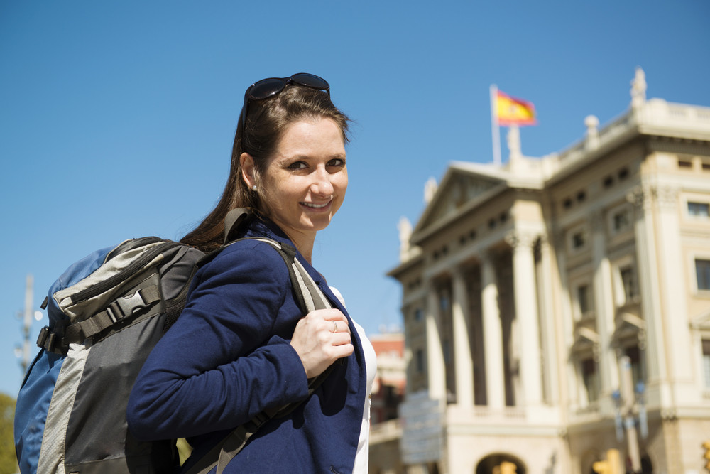 Pretty young female tourist with backpack in front of the building in Barcelona city, Spain.