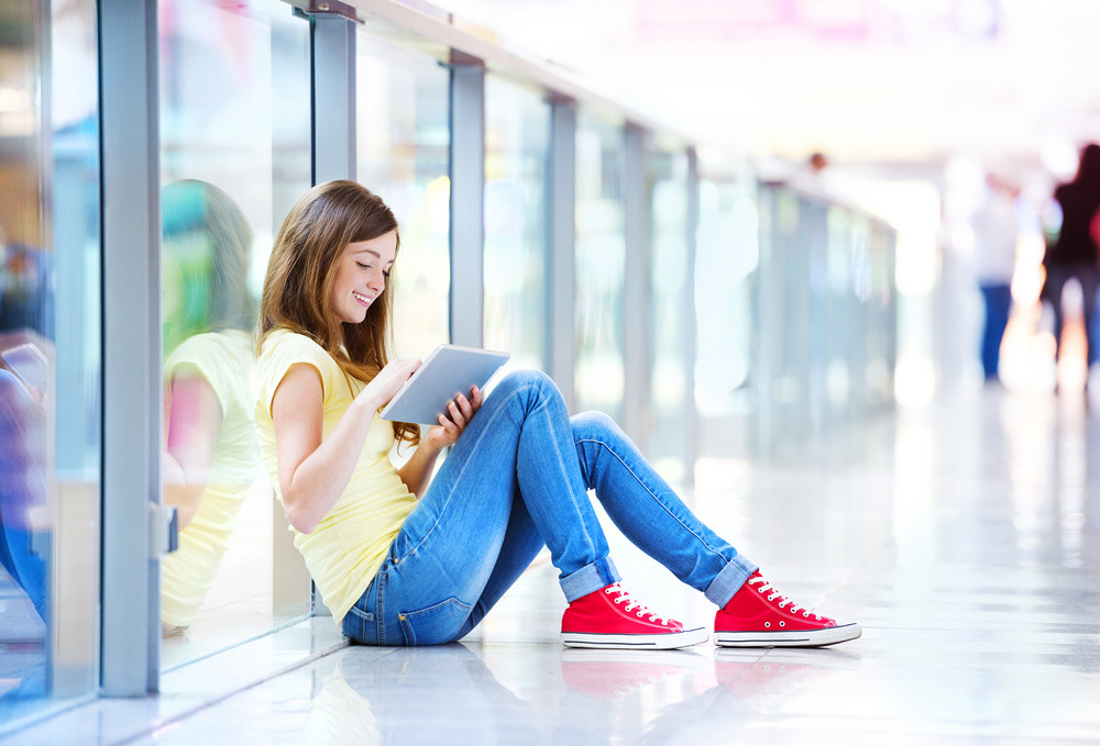Pretty young girl sitting on the floor in a shopping mall and using her tablet