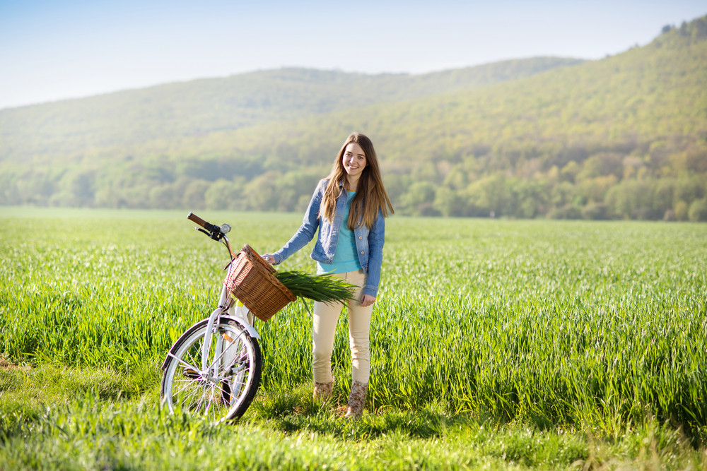 Pretty young girl with bike in green field