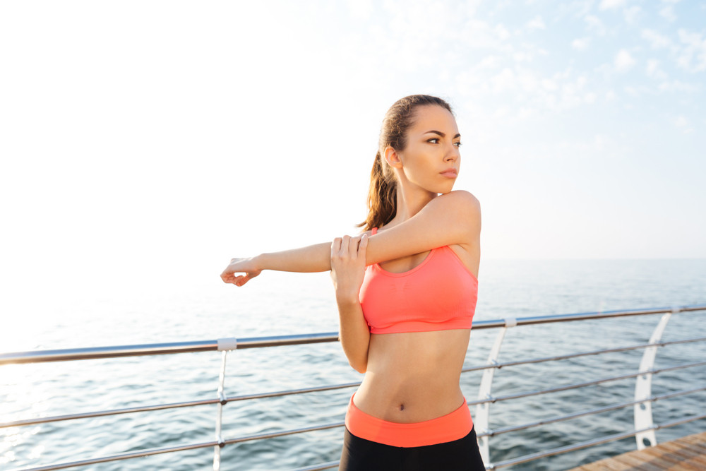 Pretty young sportswoman doing stretching exercises for hands near the sea in the morning