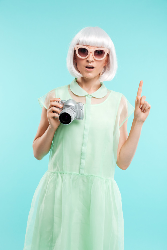 Pretty young woman fashion photographer with photo camera pointing up and having an idea