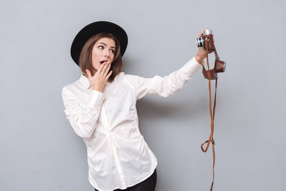 Pretty young woman in hat taking selfie with retro camera and covering her mouth isolated on a gray background