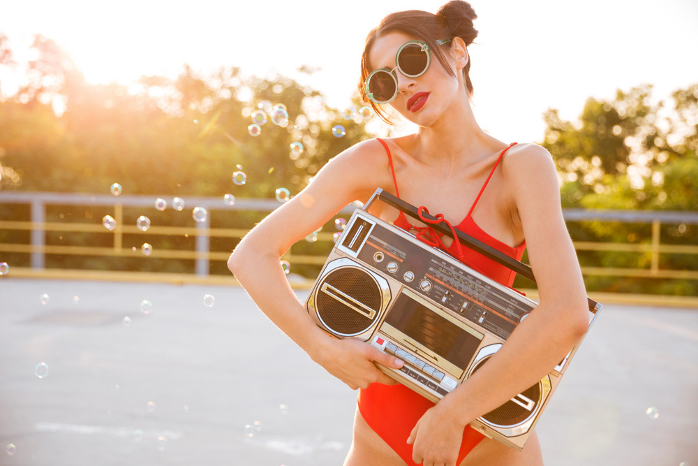 Pretty young woman in sunglasses and red swimsuit standing outdoors and holding old vintage boombox