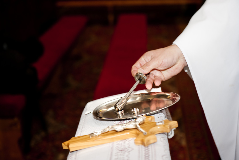 Priest blessing wedding rings during the ceremony