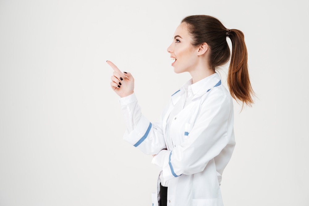 Prodile of happy surprised young woman doctor looking and pointing away over white background