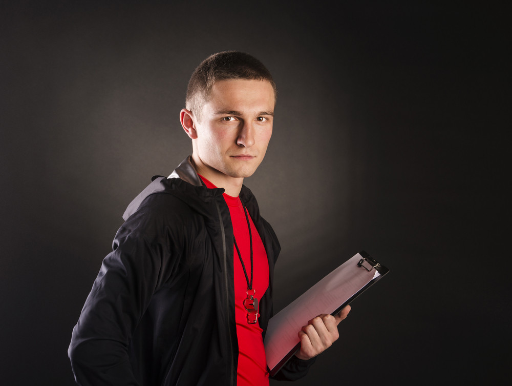 Professional fitness coach isolated on black background