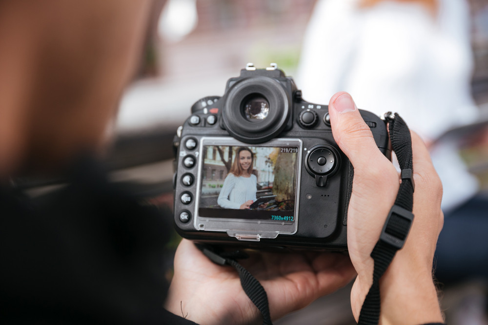 Professional photo camera holded by man photographer who taking photos of beautiful young woman in park