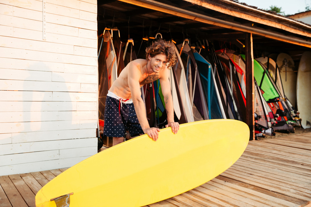 Professional young surfer getting surf board ready and looking at camera