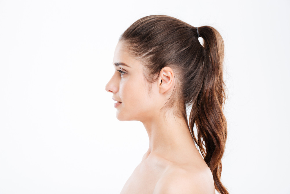Profile of attractive young woman with ponytail over white background