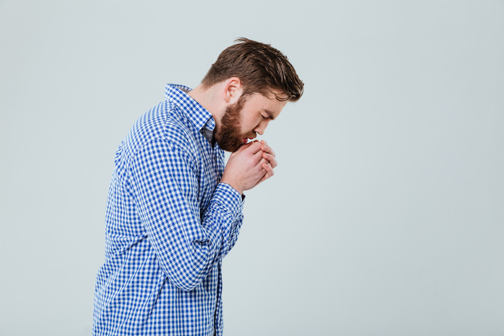 Profile of stressed young man blowing and warming his hands over white background